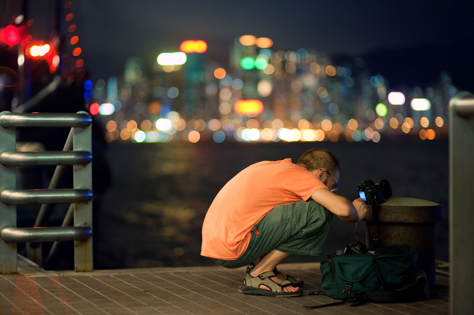A photographer looks at the back of his camera against a night time cityscape