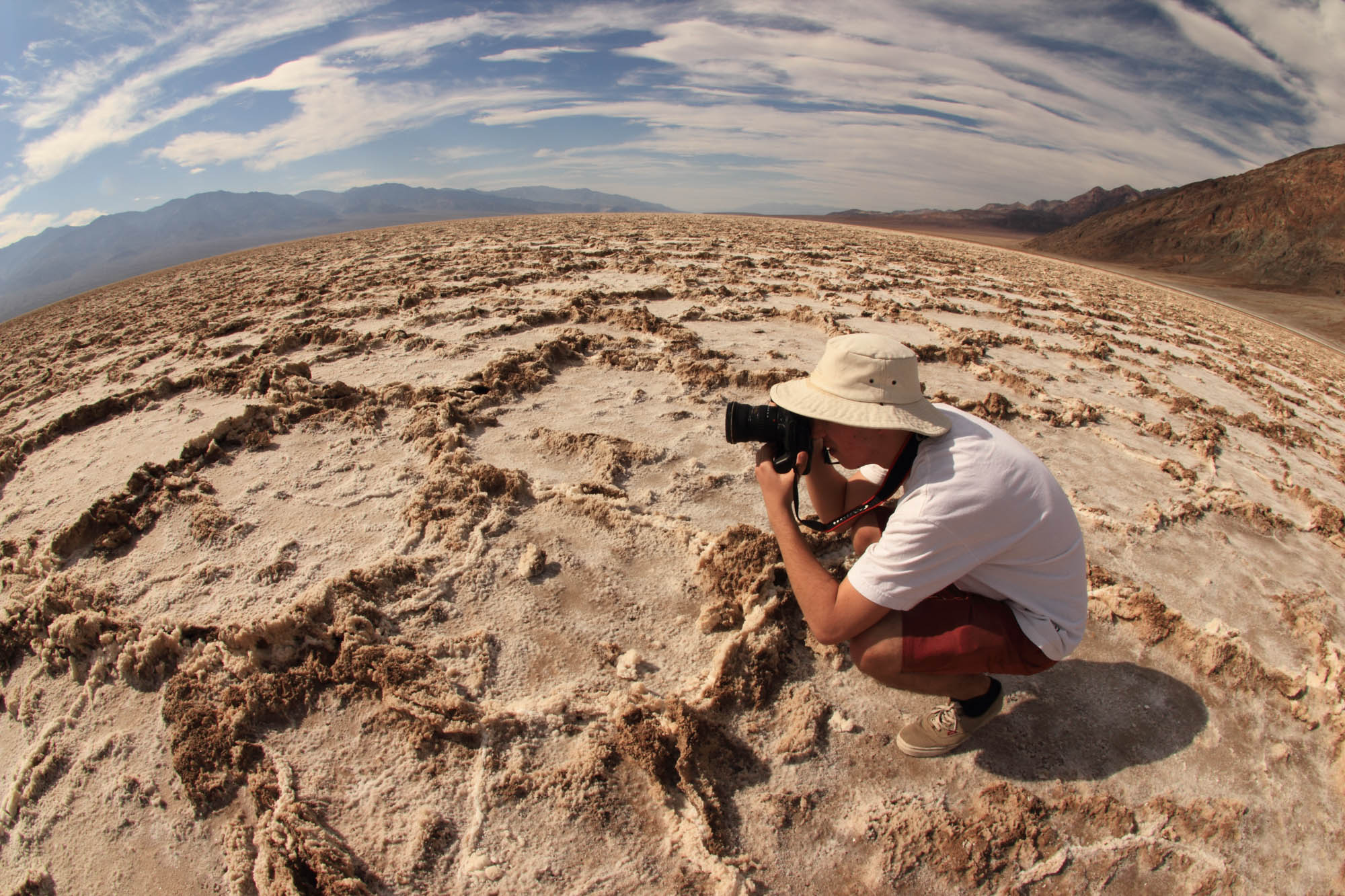 A photographer at Bad Water in Death Valley desert USA