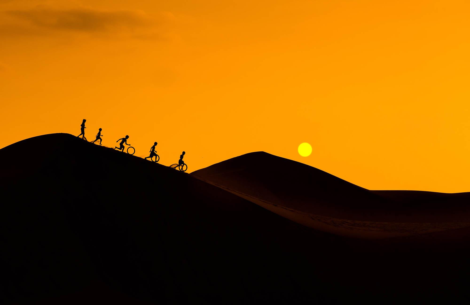 Silhouette of children playing on in the desert Vietnam