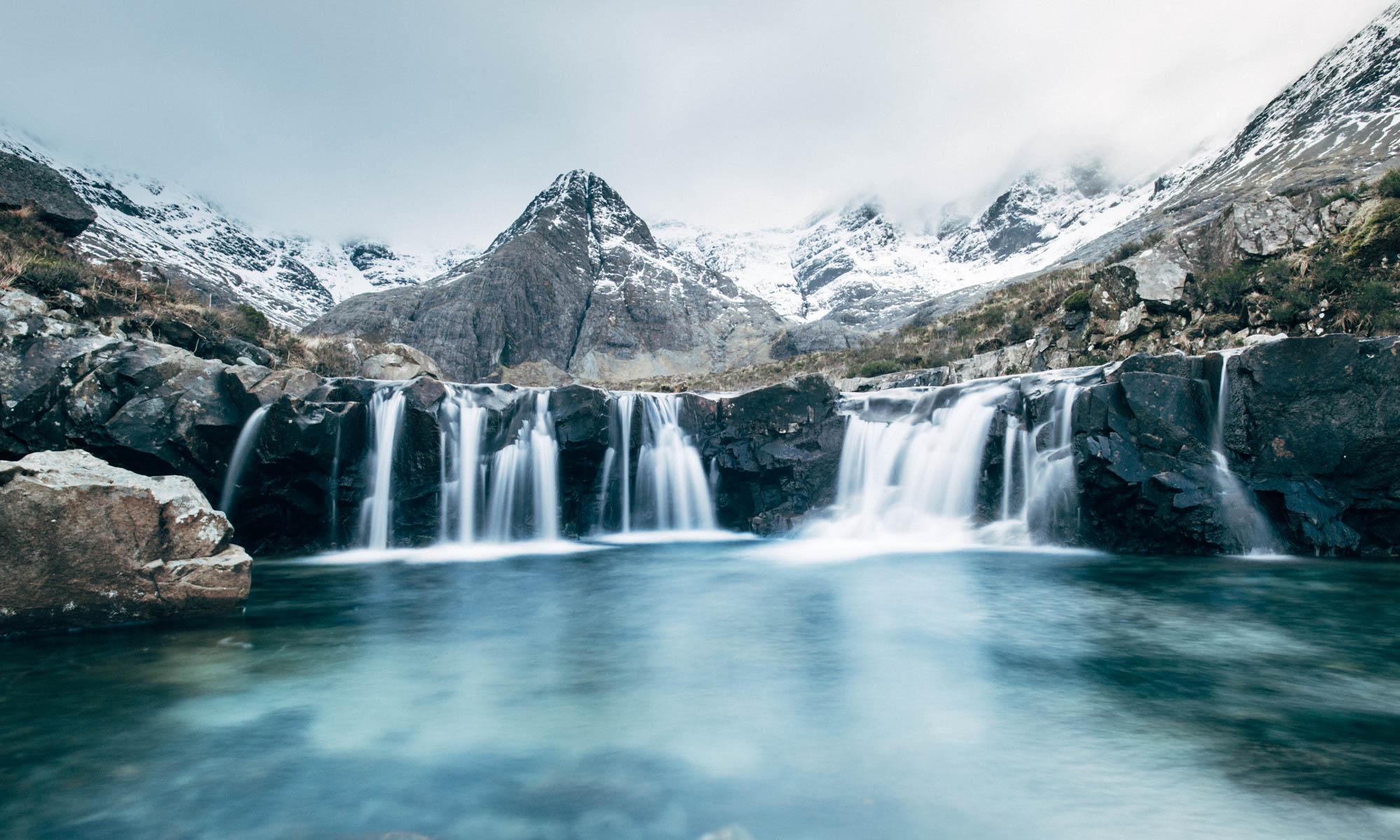 Snow melt trickles down into the blue-tinged 'Fairy Pools' on the Isle of Skye