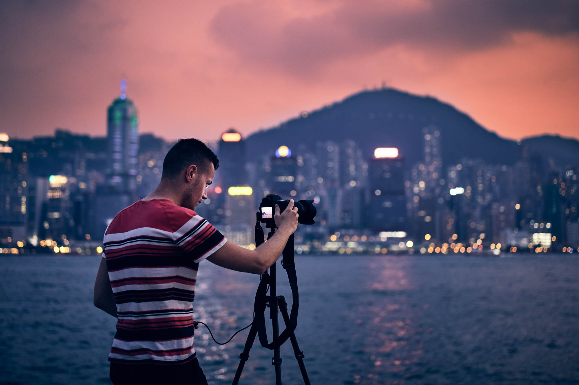 Young photographer (traveler) with tripod photographing urban skyline at sunset, Hong Kong.