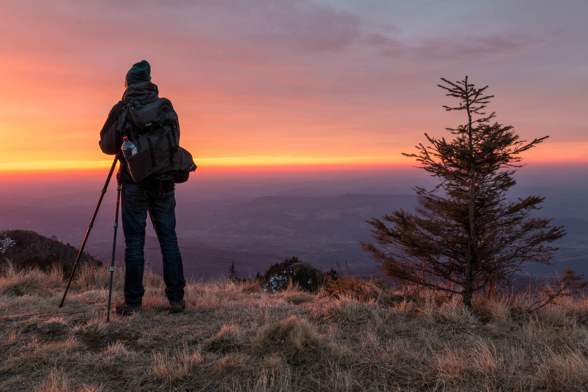 A photographer setting up the frame and capturing a sunrise in the Cozia Mountains, Romania