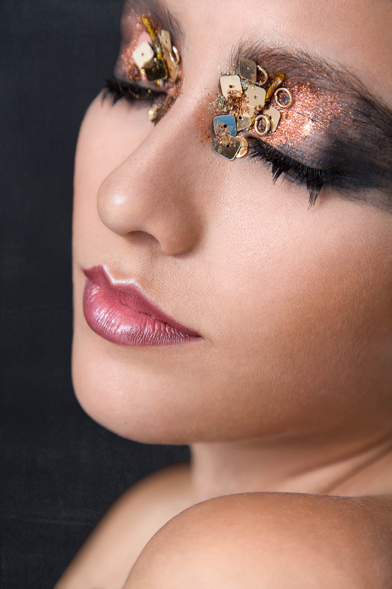 Headshot of a beauty model with extravagant make up with her eyes shut
