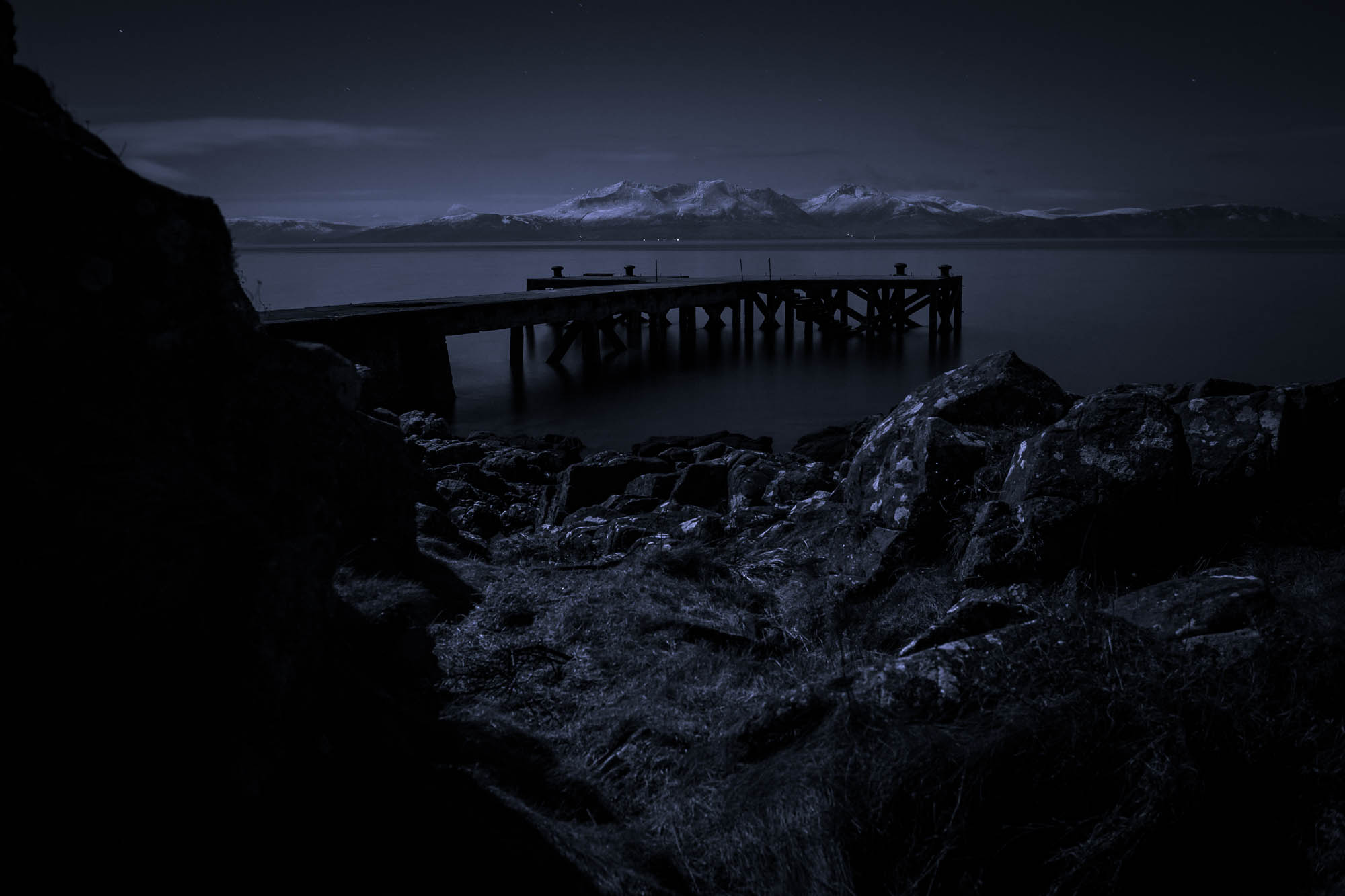 The Ayrshire hamlet of Portencross at night, looking out to the old pier, with the Isle of Arran in the distance. The sole light source is moonlight.