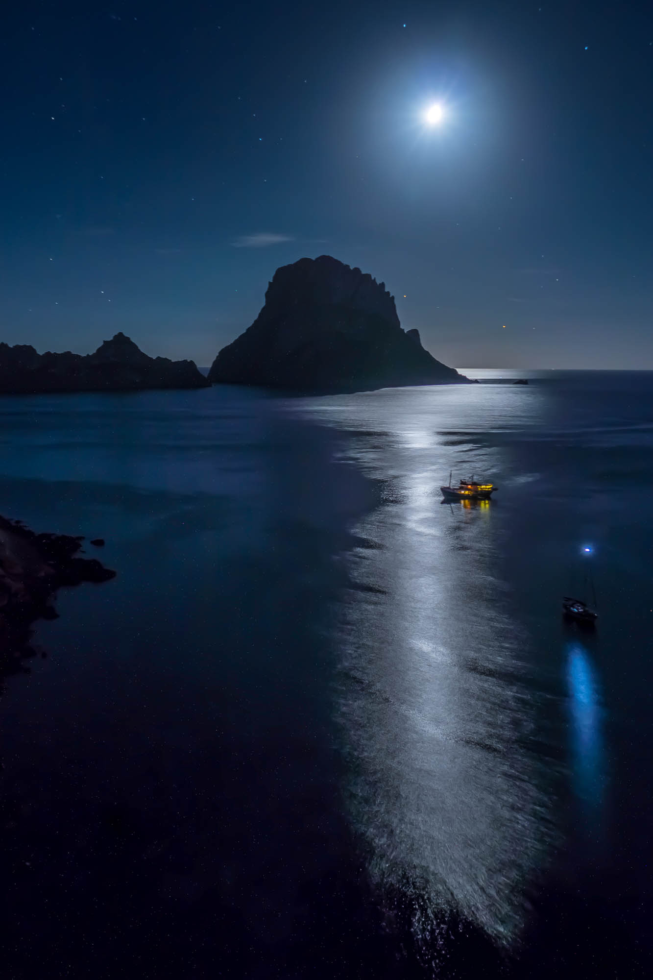 A full moon casts its reflection upon the calm sea on a warm summer evening with the spiritual rock of Es Vedra silhouetted beyond
