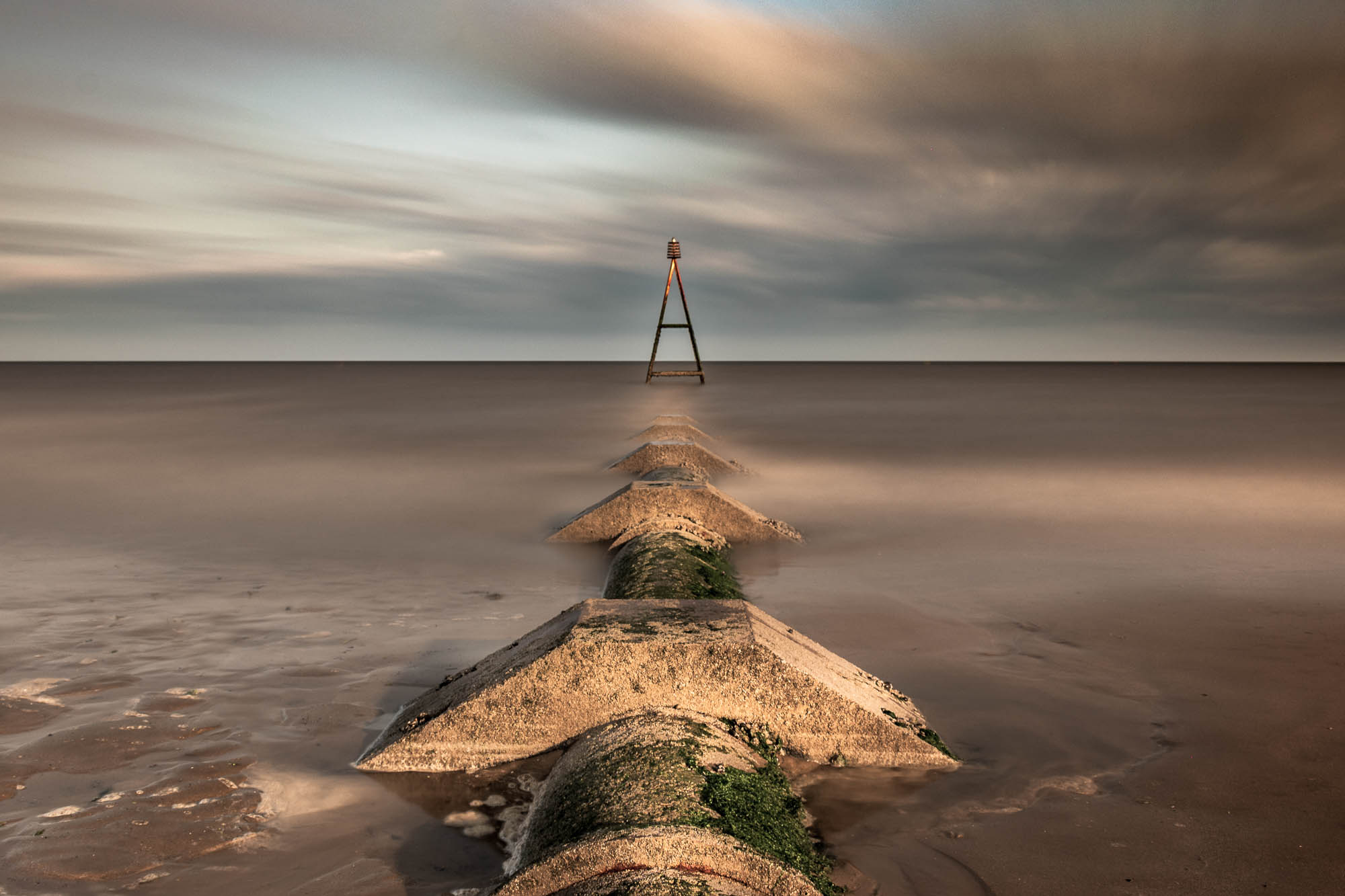 An early morning photo of a waste pipe heading out to sea at Hunstanton, England.