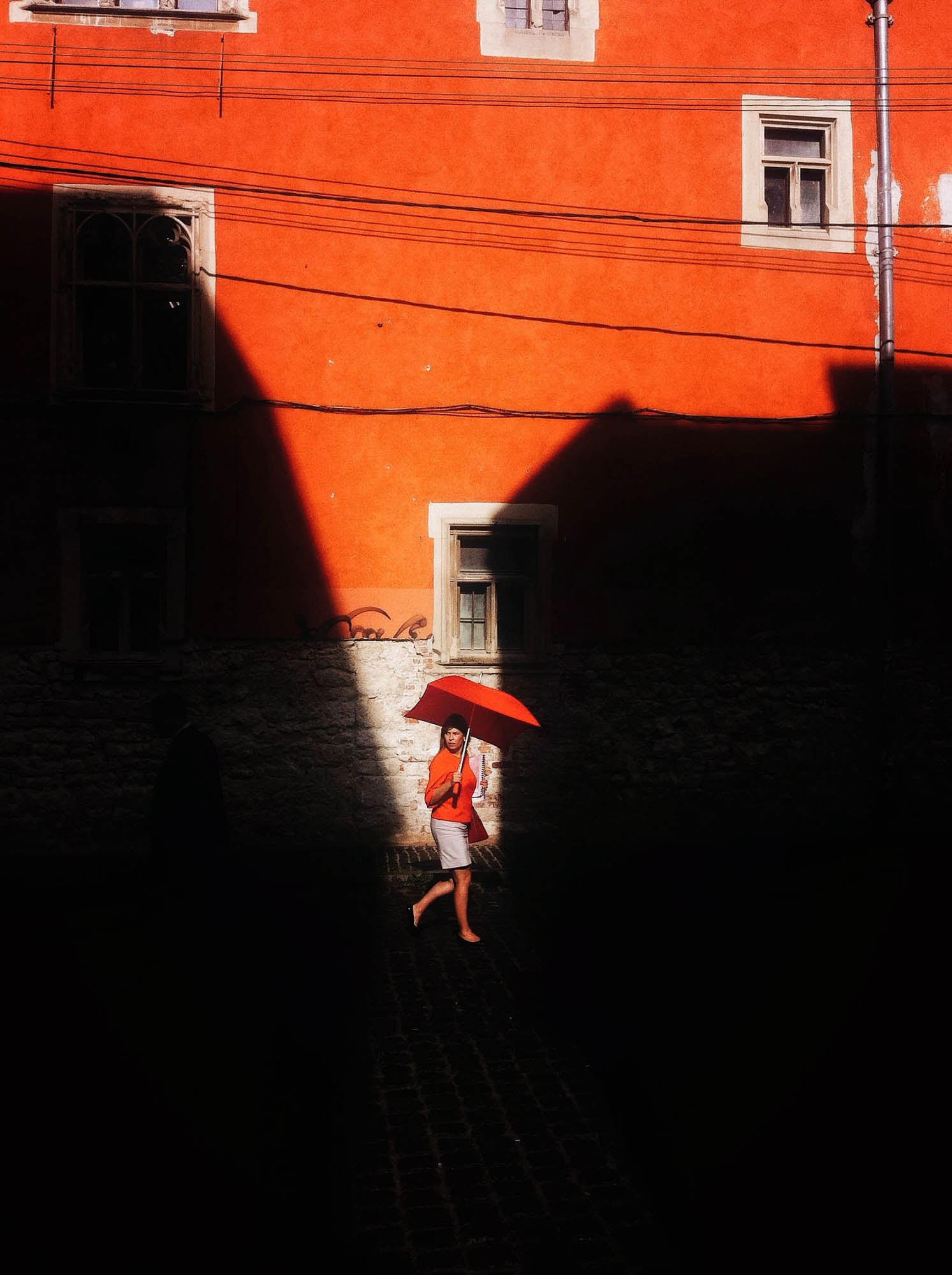 A woman dressed in a red coat walking down the street holding an red umbrella against a red wall in contrast with the black shadow.