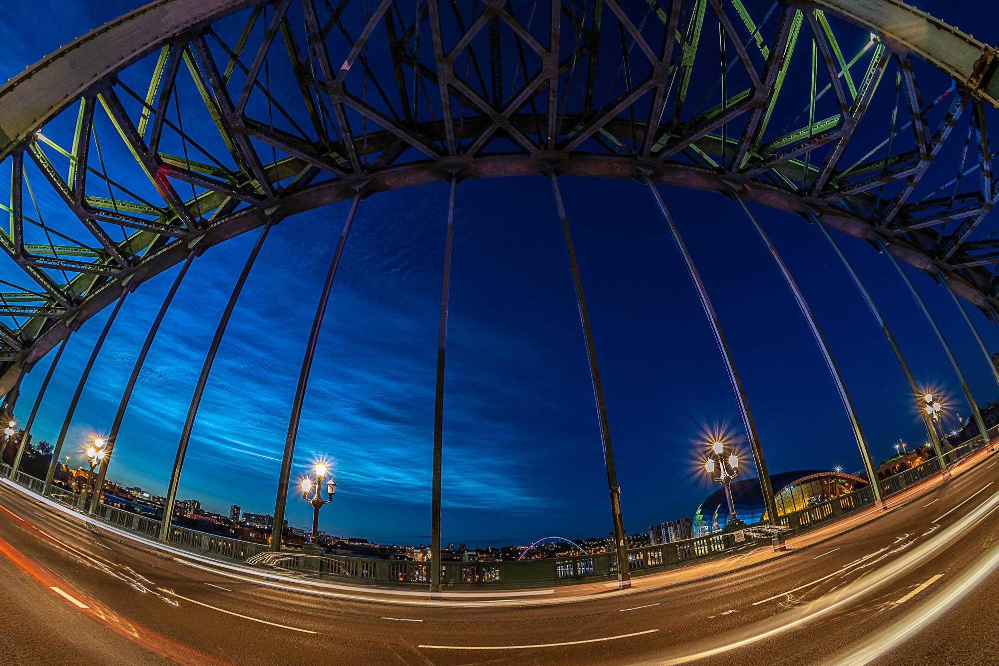 Night shot of the Tyne Bridge and the Newcastle and Gateshead quaysides on the river Tyne glowing, with rare Noctilucent clouds in the sky. Taken with a 7.5mm Fisheye lens.