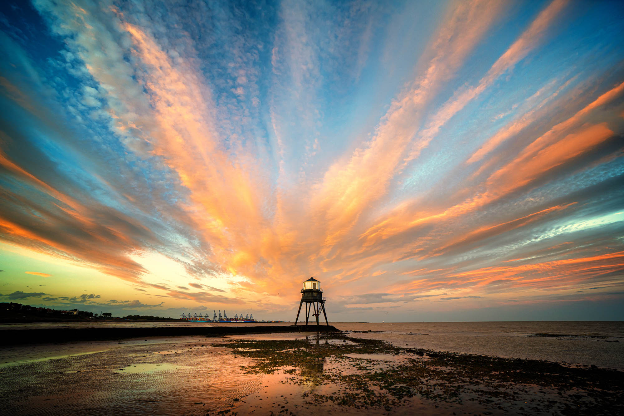 View of sunset through there passing clouds heading inwards towards the Dovercourt Low Light in Essex in August 2020