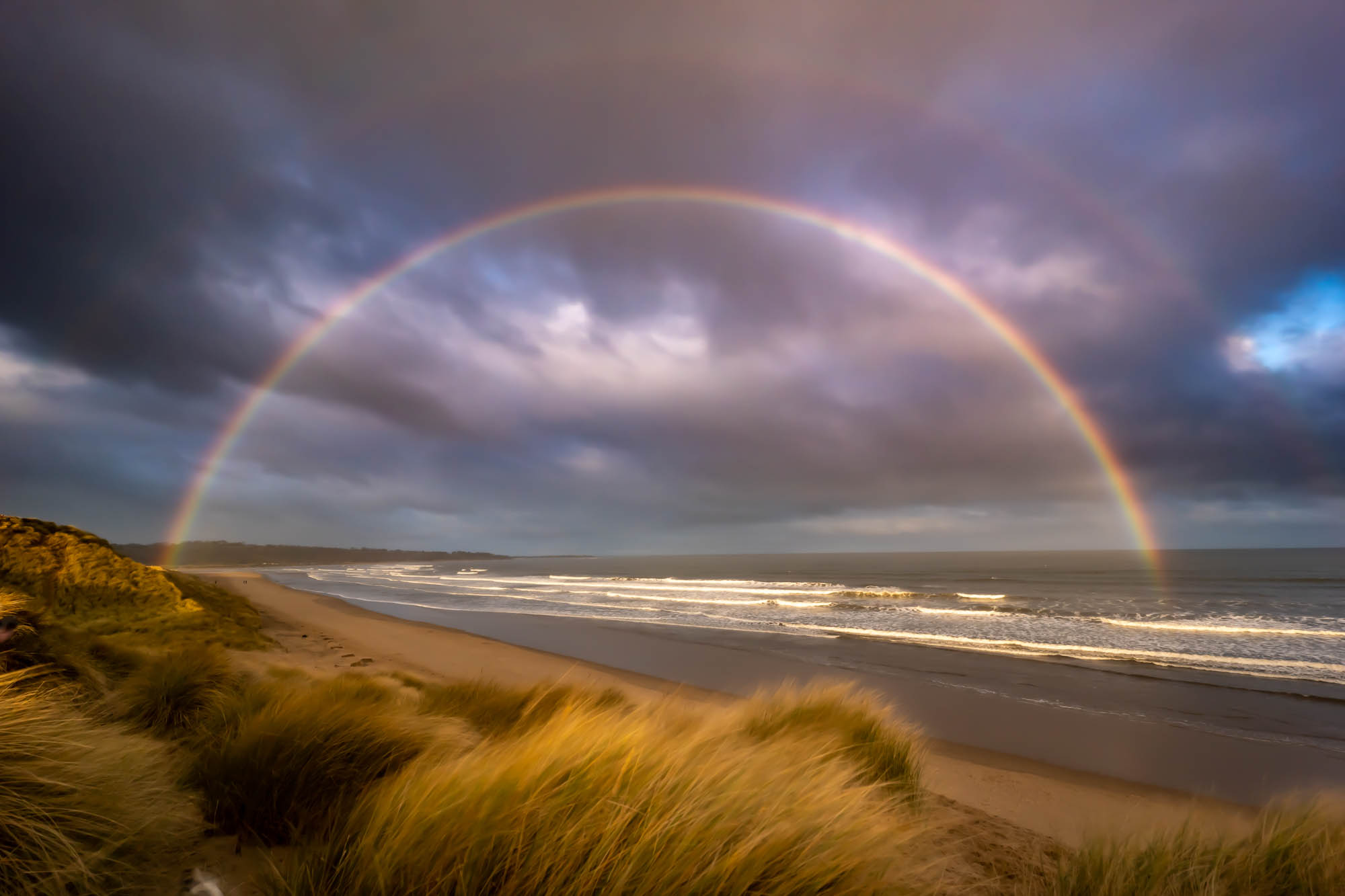 Heavy skies and a Double Rainbow on the beautiful Alnmouth Bay beach in Northumberland on New Years Day