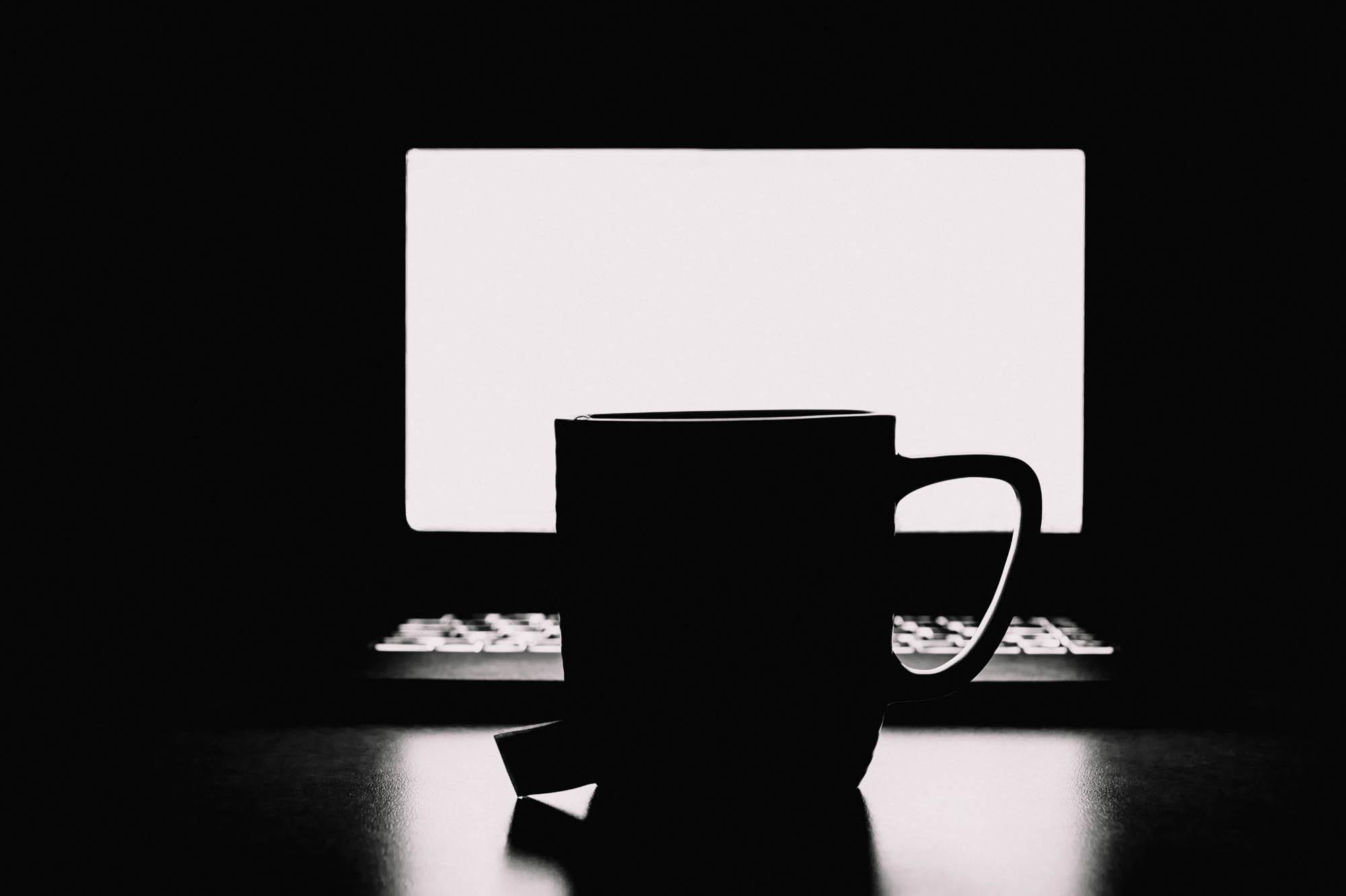 The glow of the computer screen silhouetting a mug
