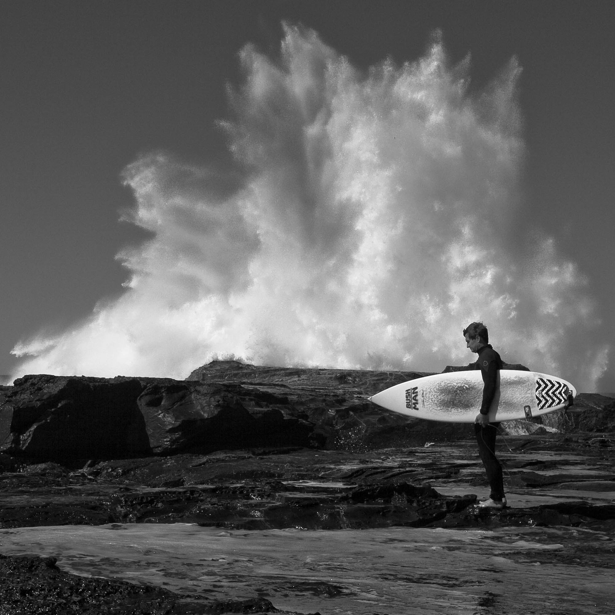 There's an art in knowing when to stop shooting, in being confident that the shot is in the bag. Black and white photo of a surfer