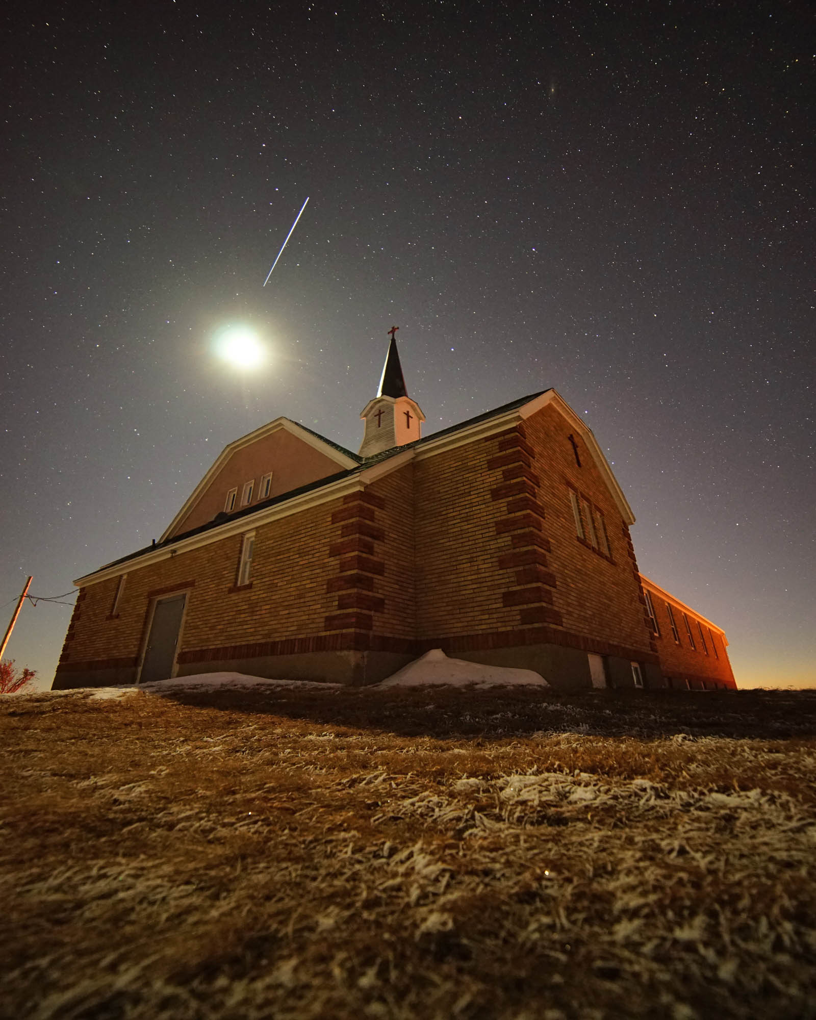 St. Vincents Catholic Church, rural Morton County, North Dakota. Moon above, with international space station flying over.