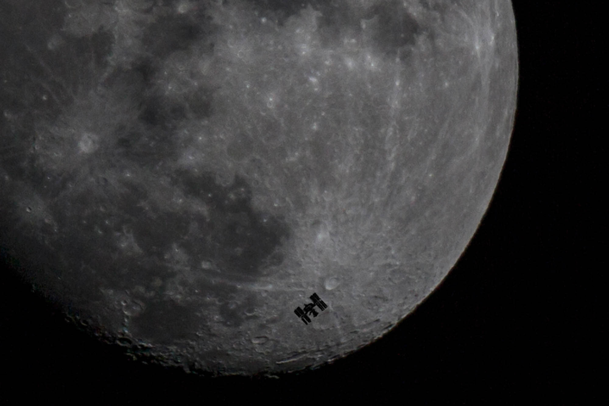 The International Space Station passing between the Moon and Earth, 260 miles in the sky.