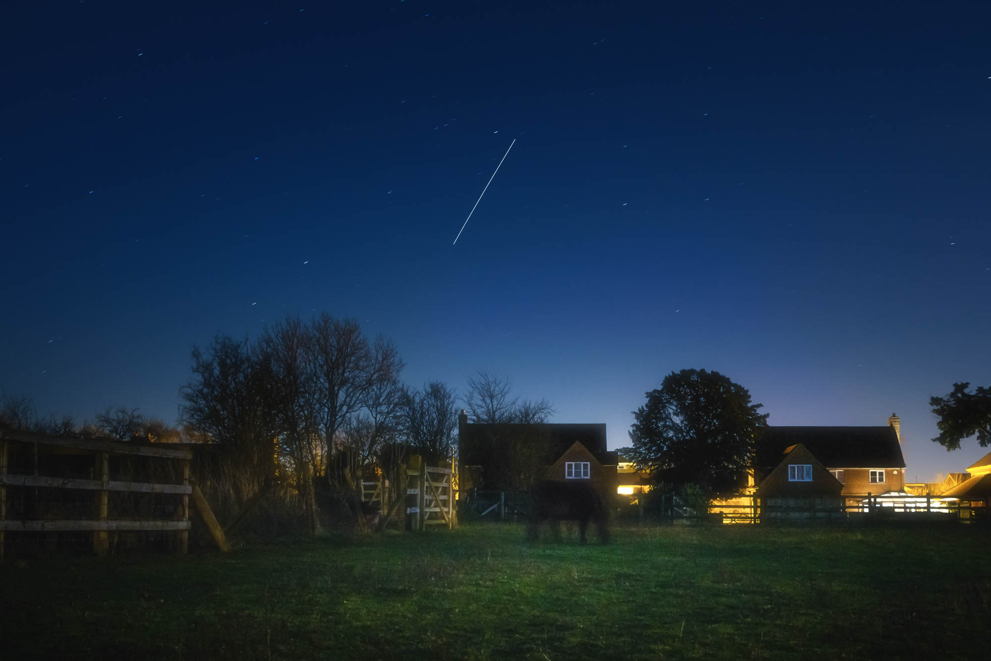 Space station captured over a suburban landscape during the blue hour