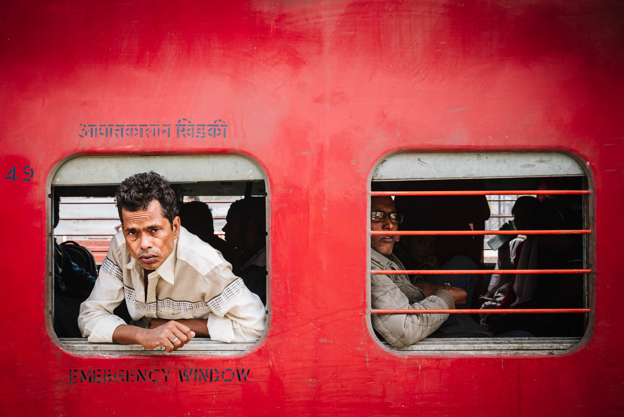 Indian train passenger peers from emergency exit of bright red Varanasi train as it sits in the station. Shot with a prime 35mm lens.
