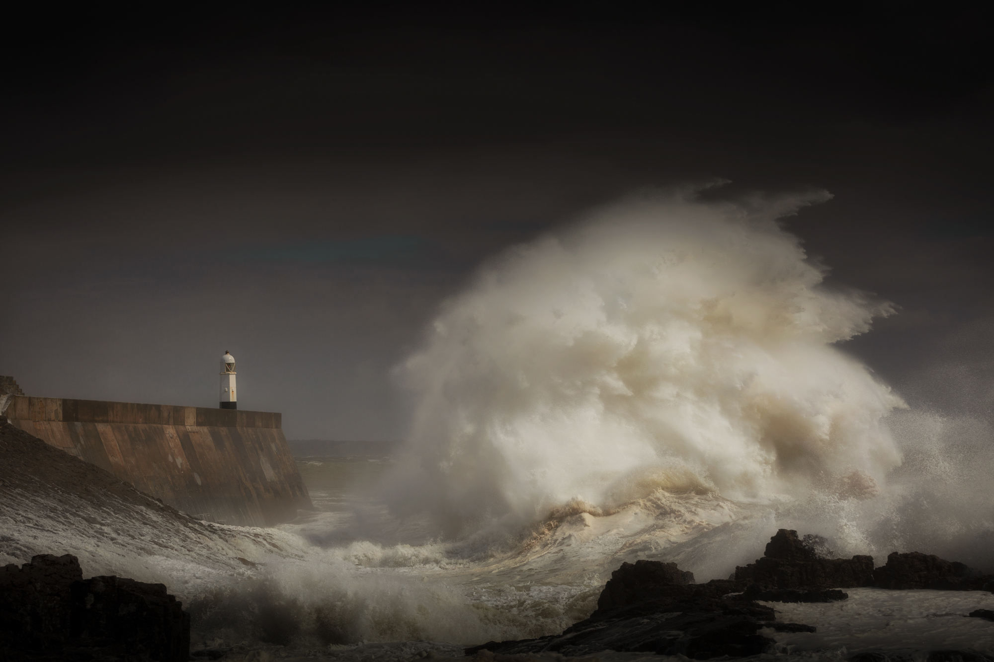 Porthcawl lighthouse and pier in the jaws of a storm on the coast of South Wales, UK