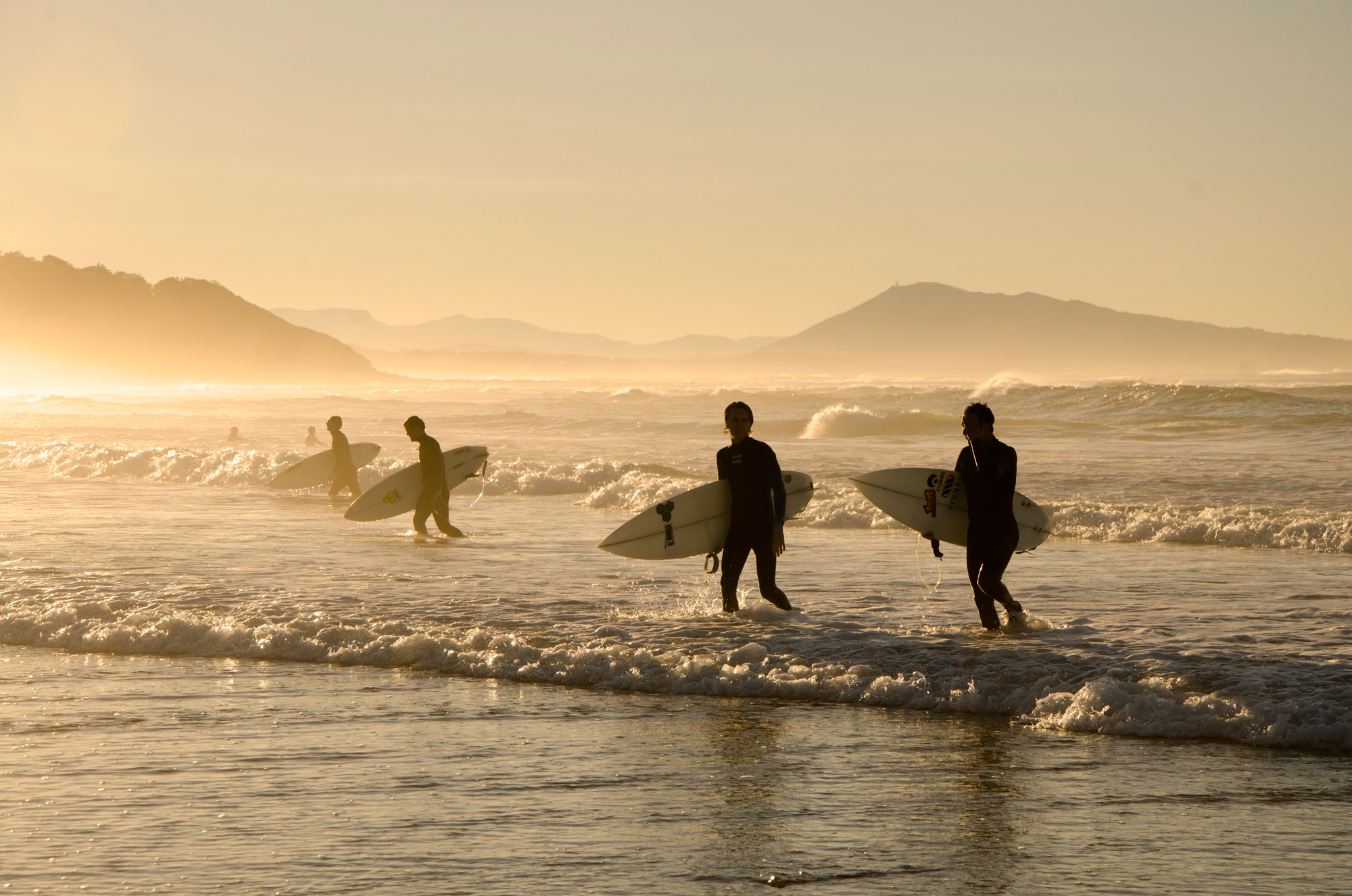 Surfers leaving the waves behind at a beach near Biarritz during sunset, France.