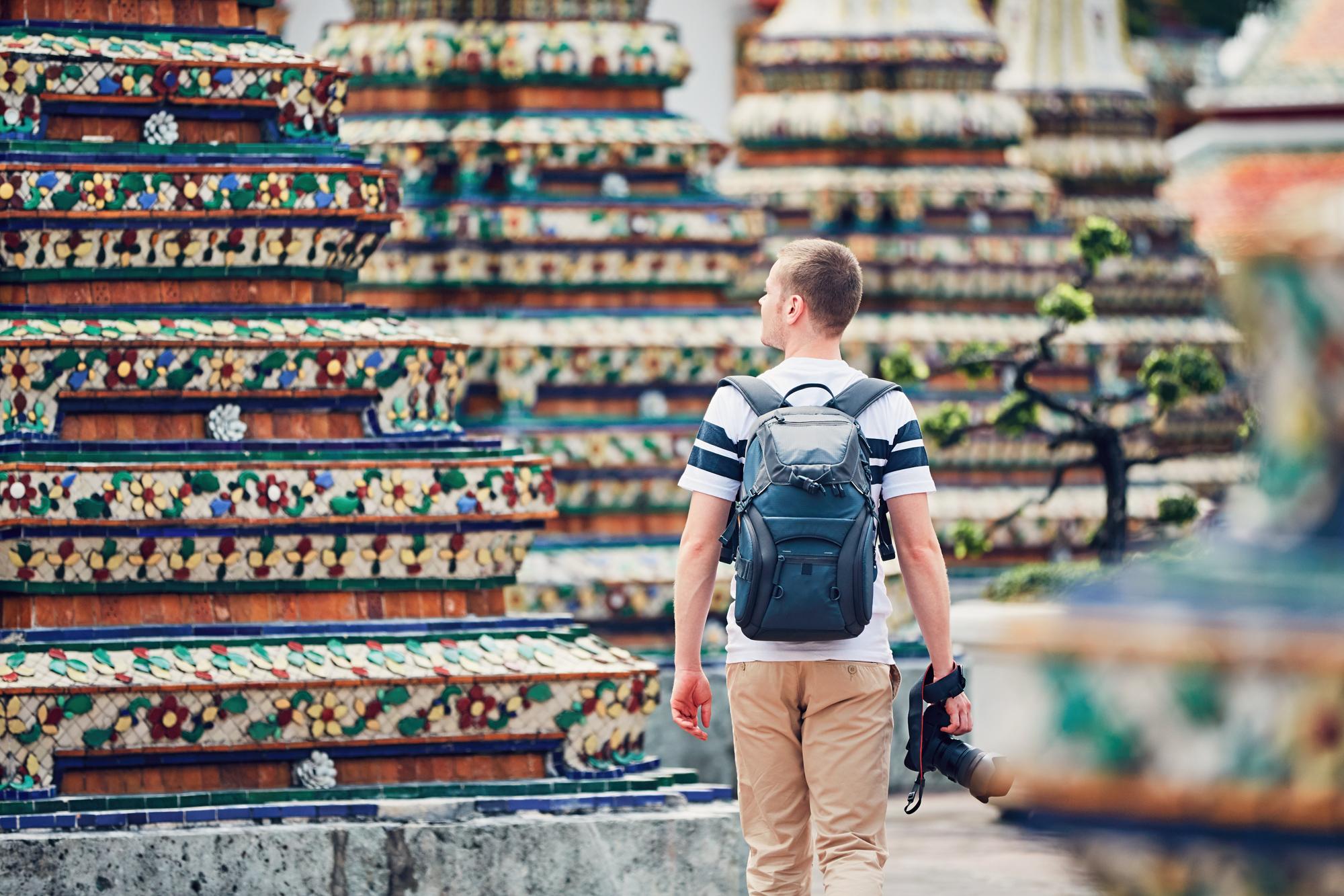 Young photographer (traveler) with photo camera walking in Wat Pho temple. Bangkok, Thailand