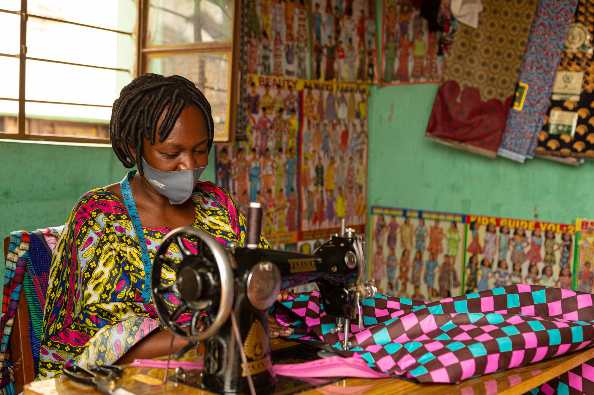 An environmental portrait of a tailor making a bag on her sewing machine. This image was captured in Nyamirambo, Kigali.