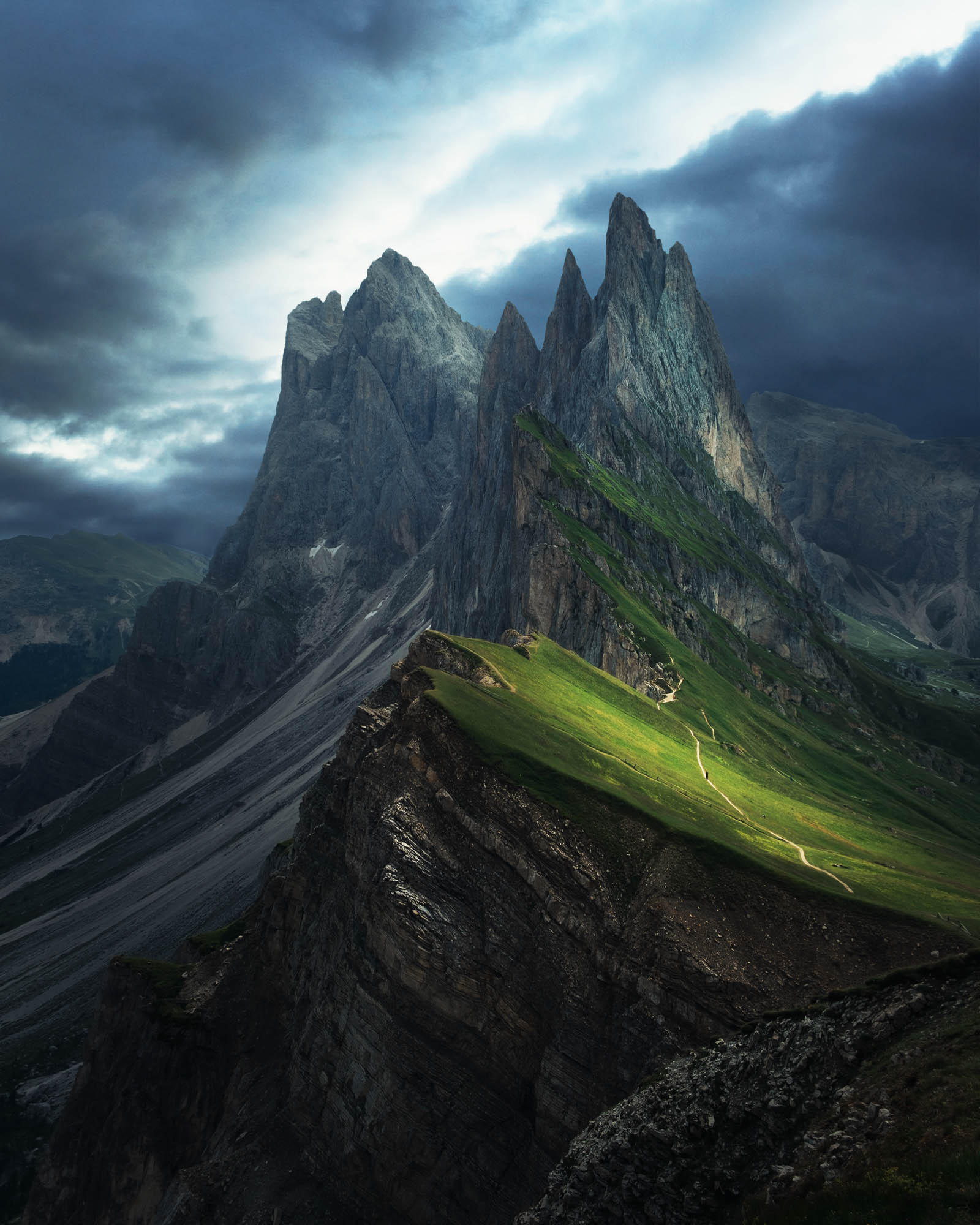 A picture of the Seceda mountain range in the northern Italian Dolomites. It is very dark and moody with light casting on the mountains. There is one man walking on the path.