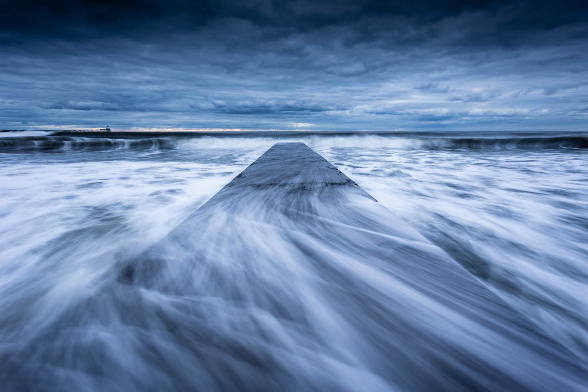 Waves sweep across the concrete jetty at Blyth Beach on the Northumberland coast. Enhanced with Photoshop's new Super Resolution feature.