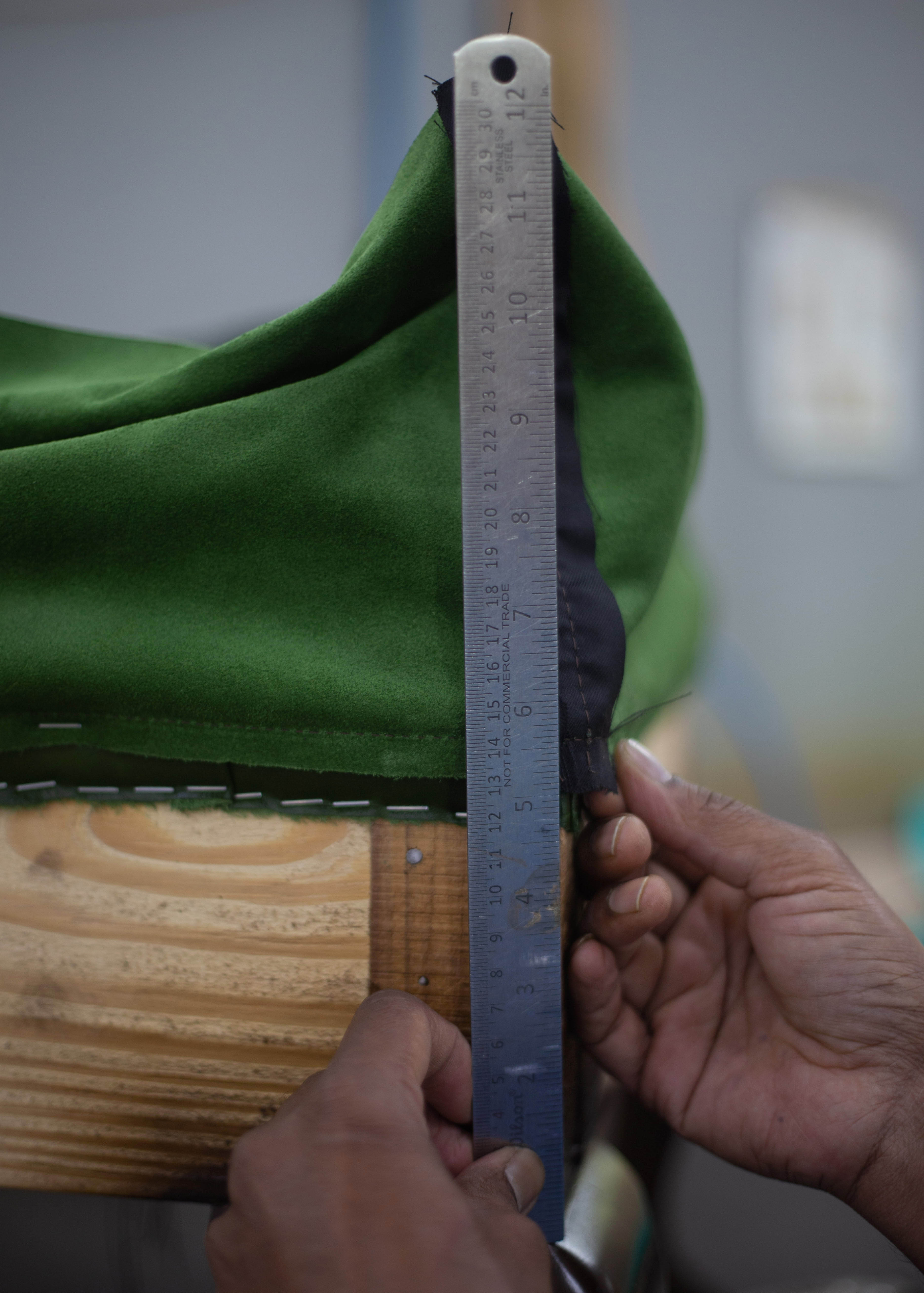 man measuring the length of fabric