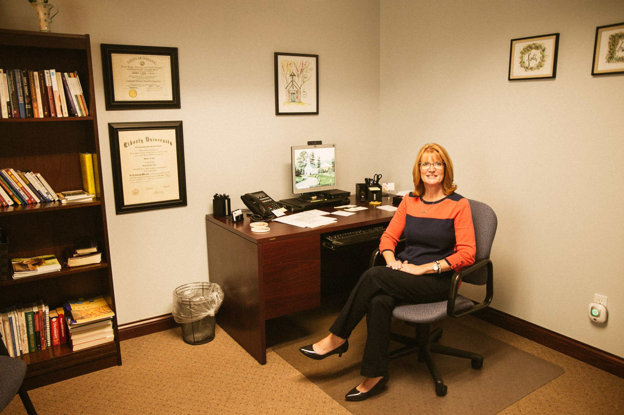 A counselor sits with a welcoming smile in her office.