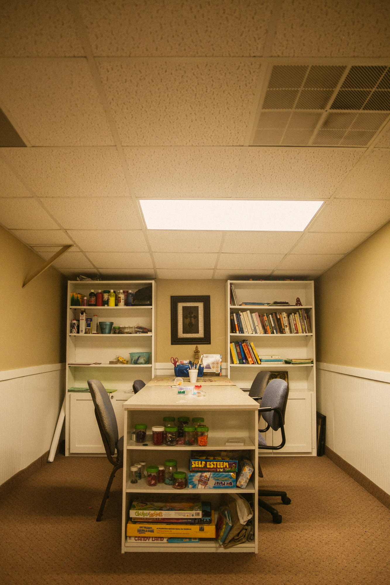 An empty play therapy room with assorted craft items on the table