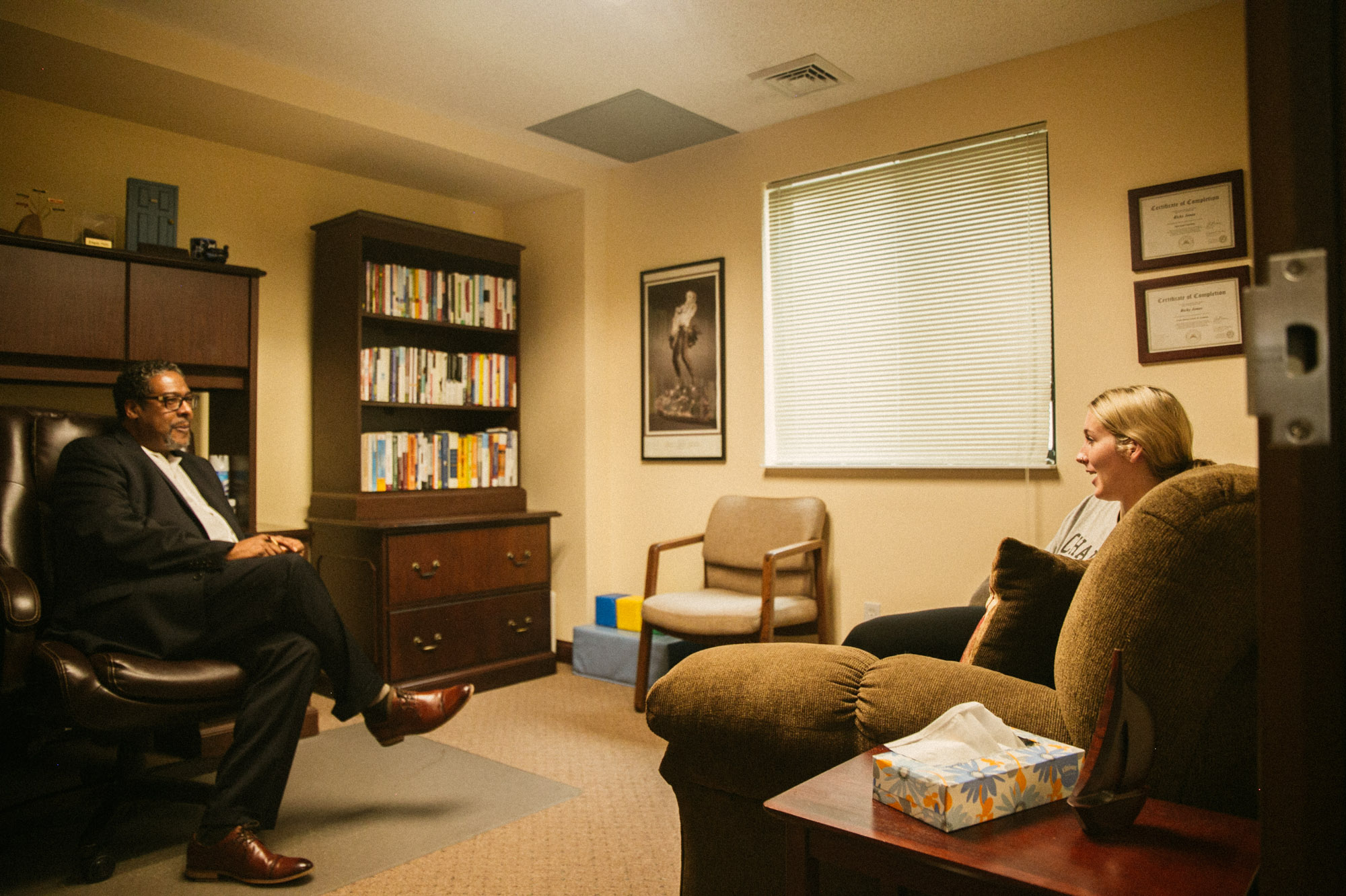 A counselor sits in his office and chats with a client sitting on a couch
