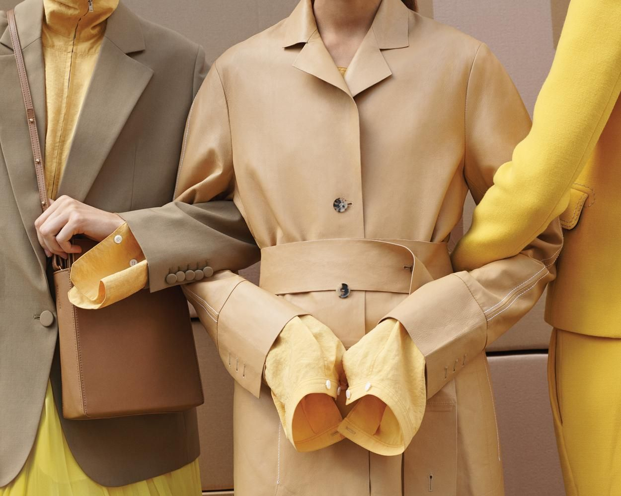 three people with their arms linked showing only the torso and wearing yellow suits