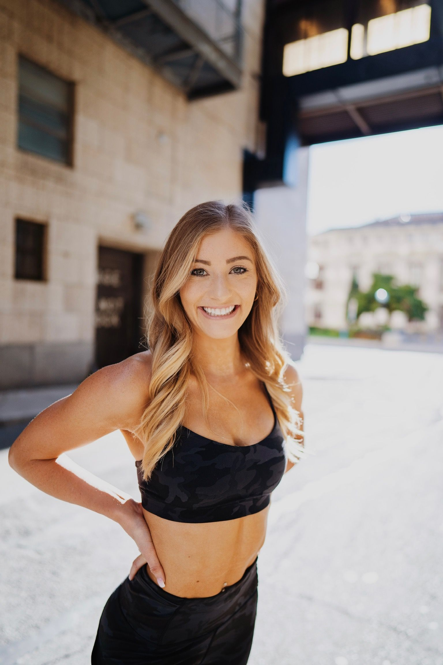 Kyle Bea in black workout apparel closeup smiling with hands on hips