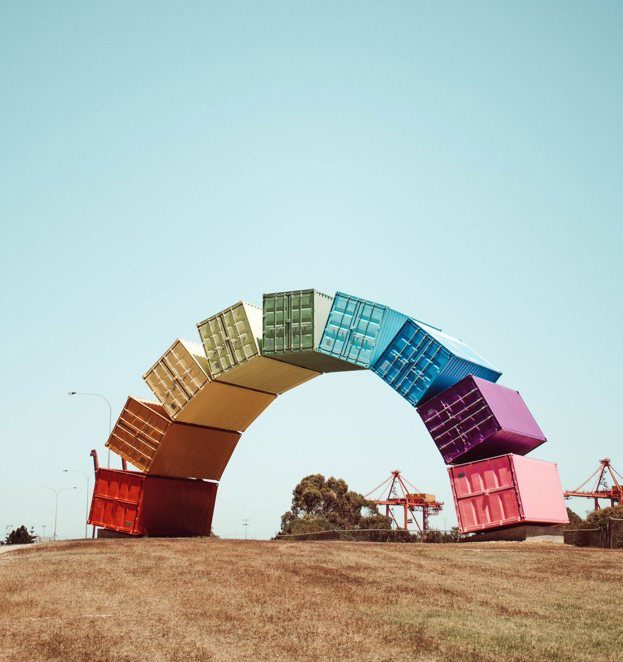 Picture of colourful shipping crates in a rainbow formation, depicting gay pride.