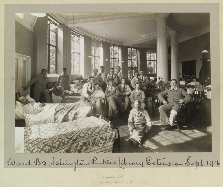 """An old photography displaying men in a variet of uniforms posing, some on beds. The caption reads """" Ward B2 Islington Public Library Extension Sept 1916"""""""