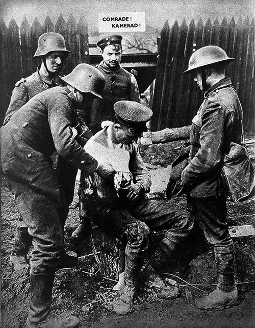 """An old photo of four soldiers stood around an injured soldier in the foreground. A caption reads """"COMRADE! KAMERAD!"""""""