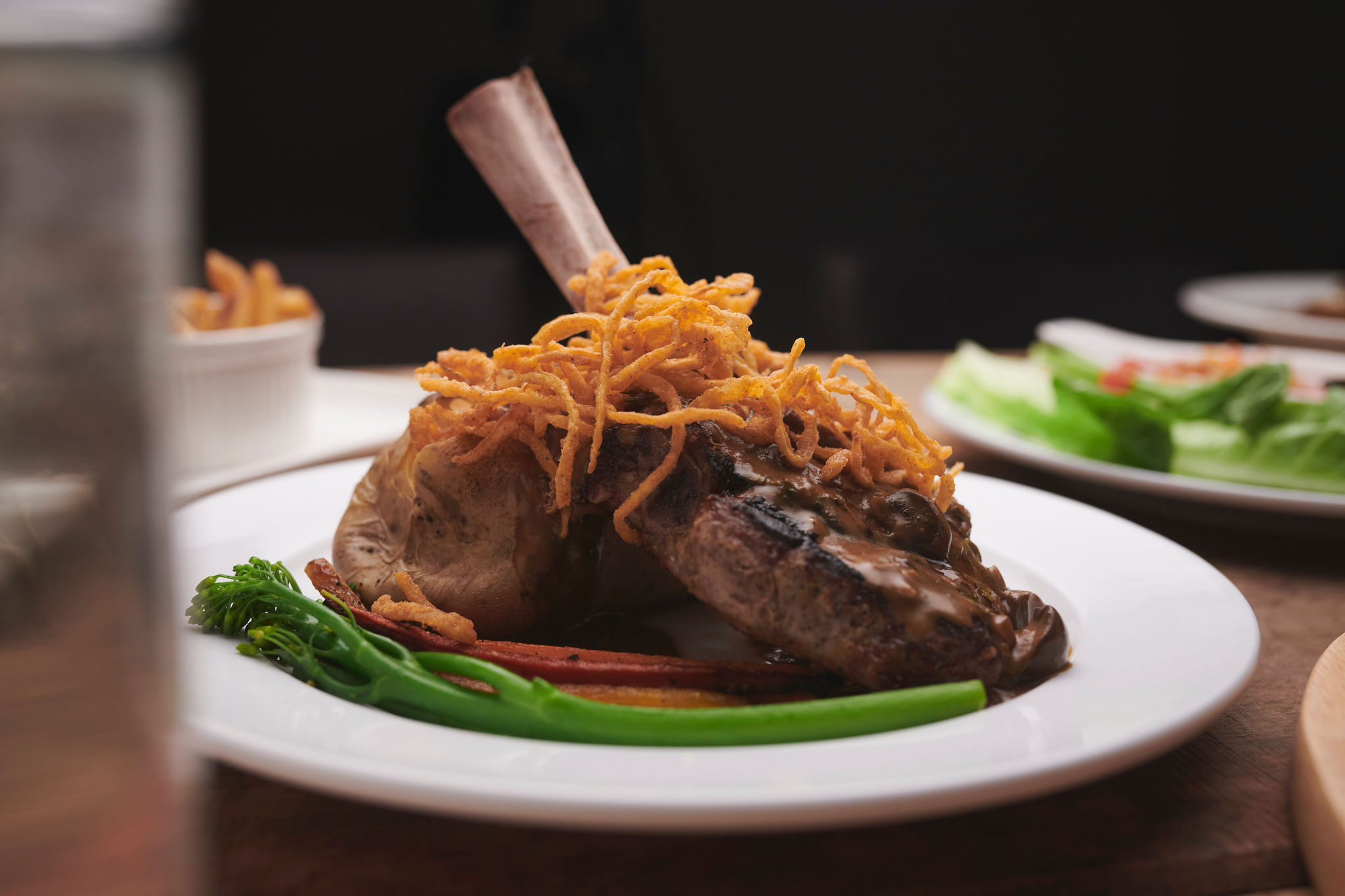 A bone-in lamb chop upright on an angle in the middle of a white circular plate, with vegetables on the side.