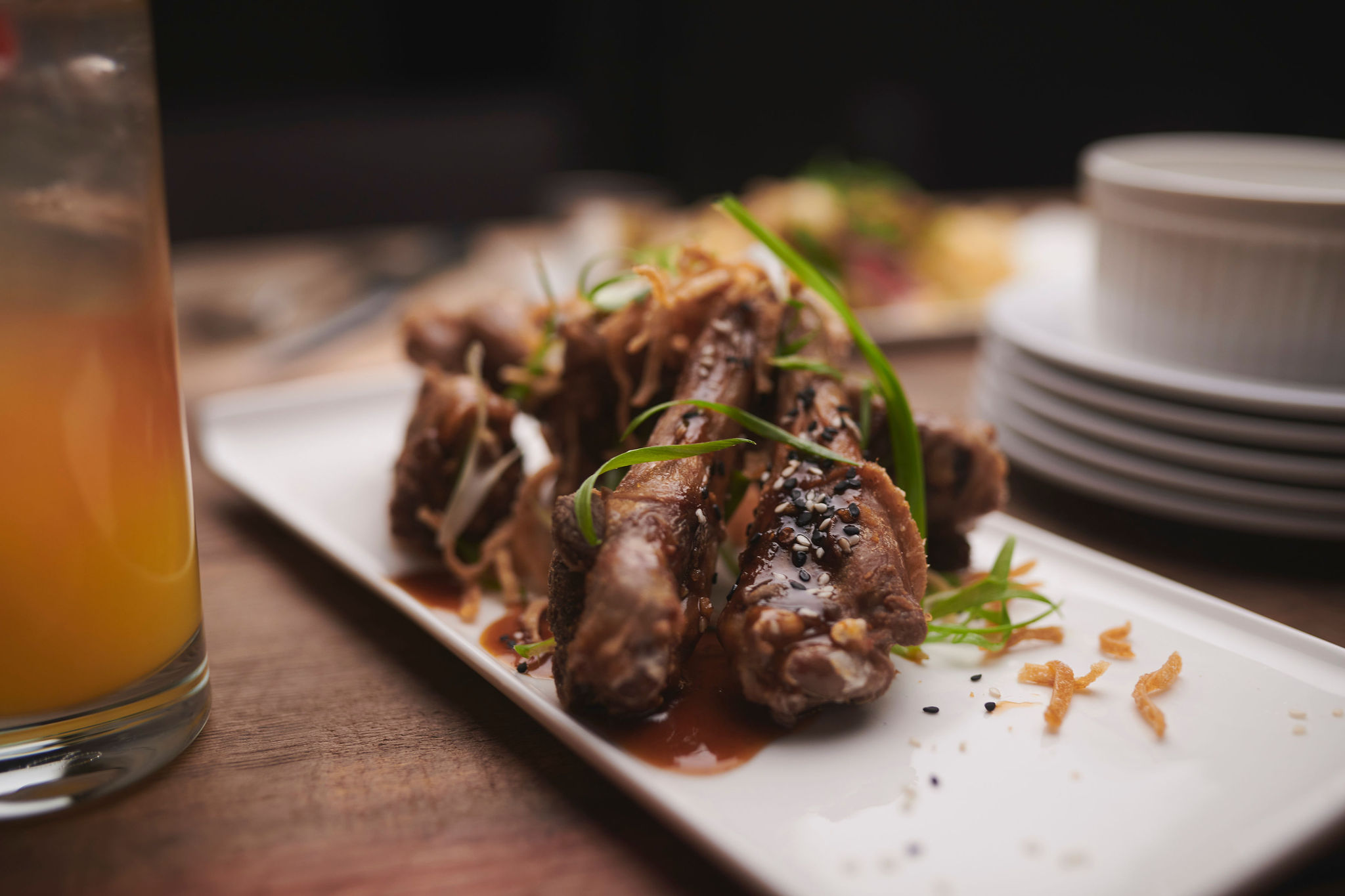 An appetizer of duck drumettes on a white plate.