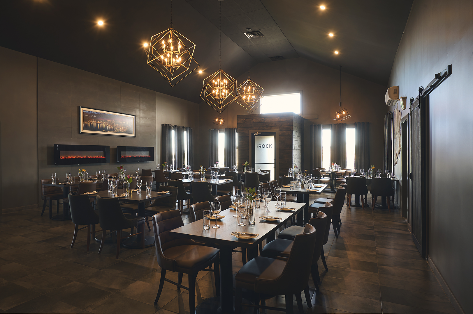 A photo of our East Wing, showing the full room with tables and chairs, and beautiful lighting.