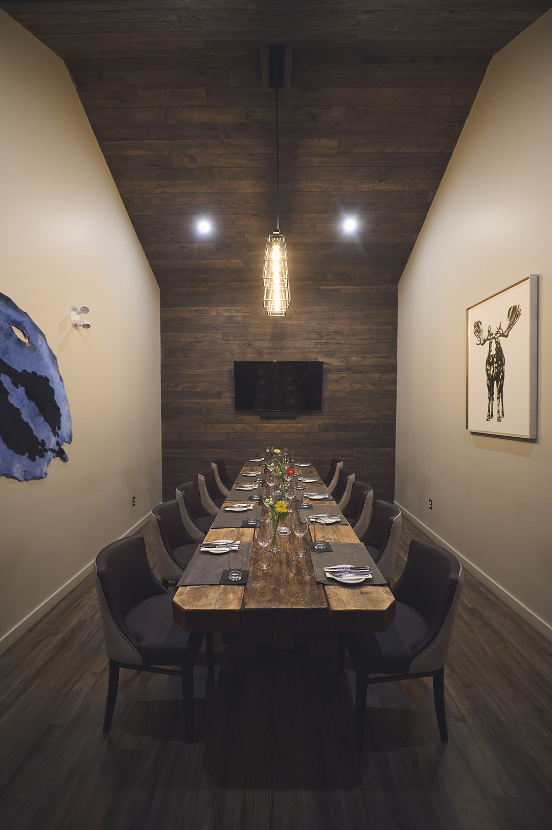 A photo of the private dining room, showing a hand made cedar table with 6 chairs on each side. On the left wall is a seal pelt dyed blue; on the right wall is an art print of a moose.