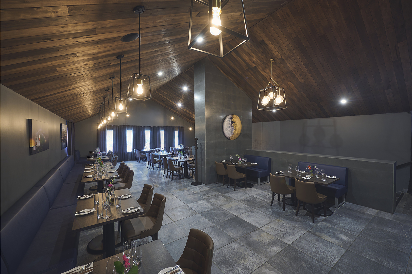 A photo of our main upstairs dining room, showing beautiful wood walls, contemporary lighting, bench seating, and tables and chairs.
