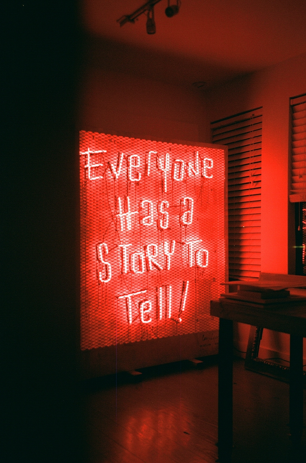 "Film photo of Neon sign ""Everyone has a story to tell"" in Miami office, cr-eate"