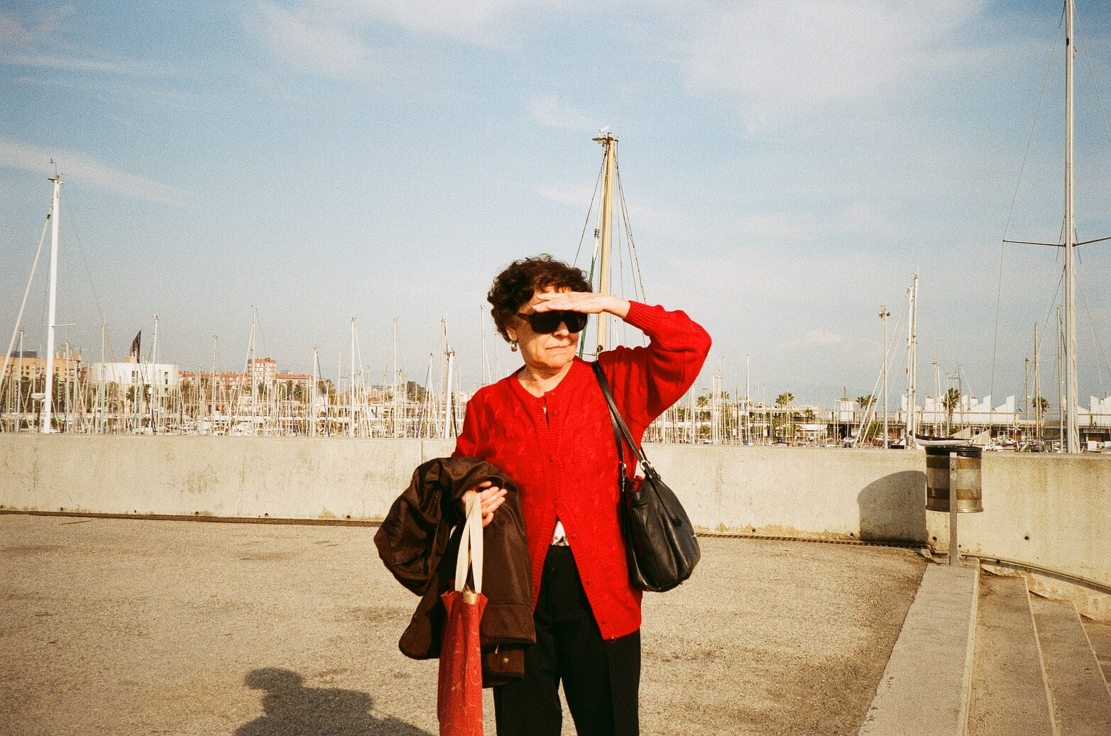 Woman in red sweater in Barcelona Streets near the water