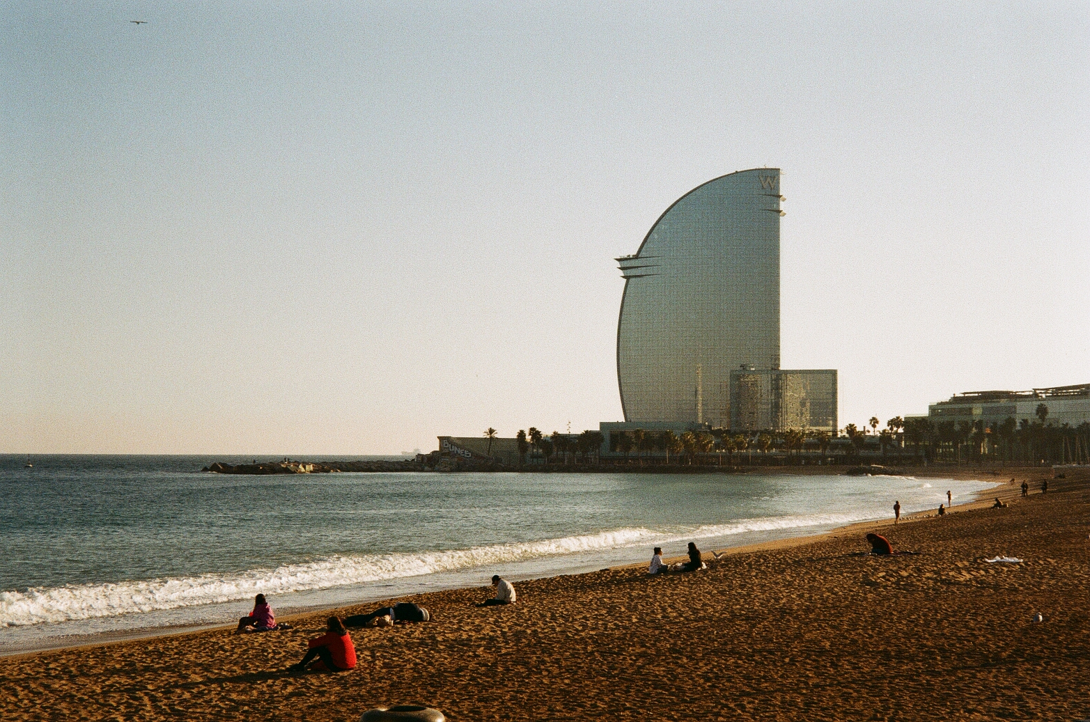 Film photo of Barcelona Beach with the famous W hotel in the background, that is shaped like a fin.