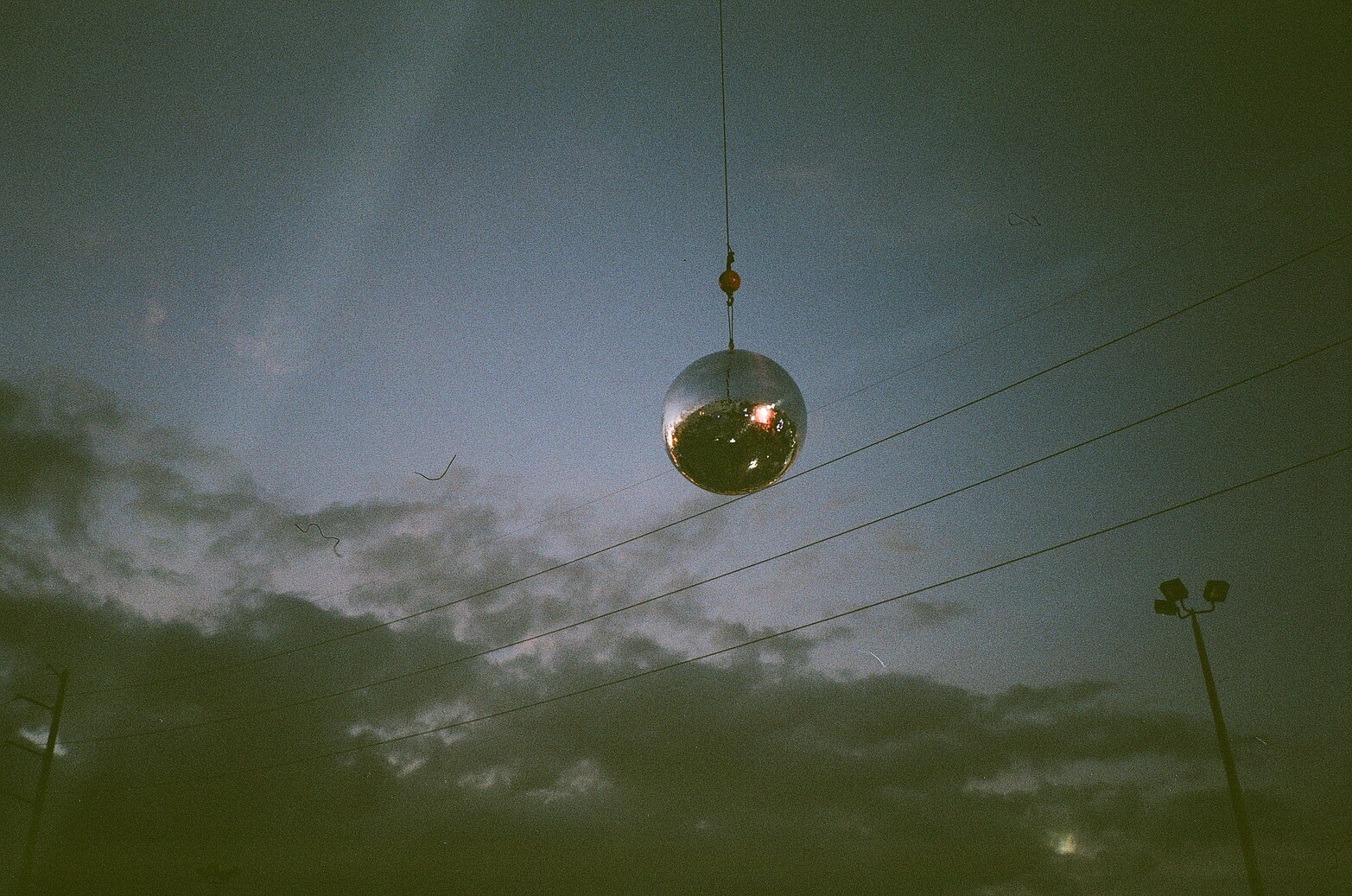 iii points disco ball film photo with sky background