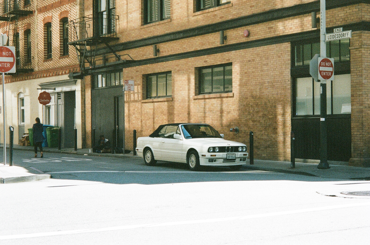 White BMW near brick walls in the streets of SF, captured on Film