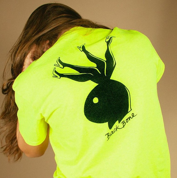 Model wearing highlighter yellow shirt with Bunny Backbone graphic on the back