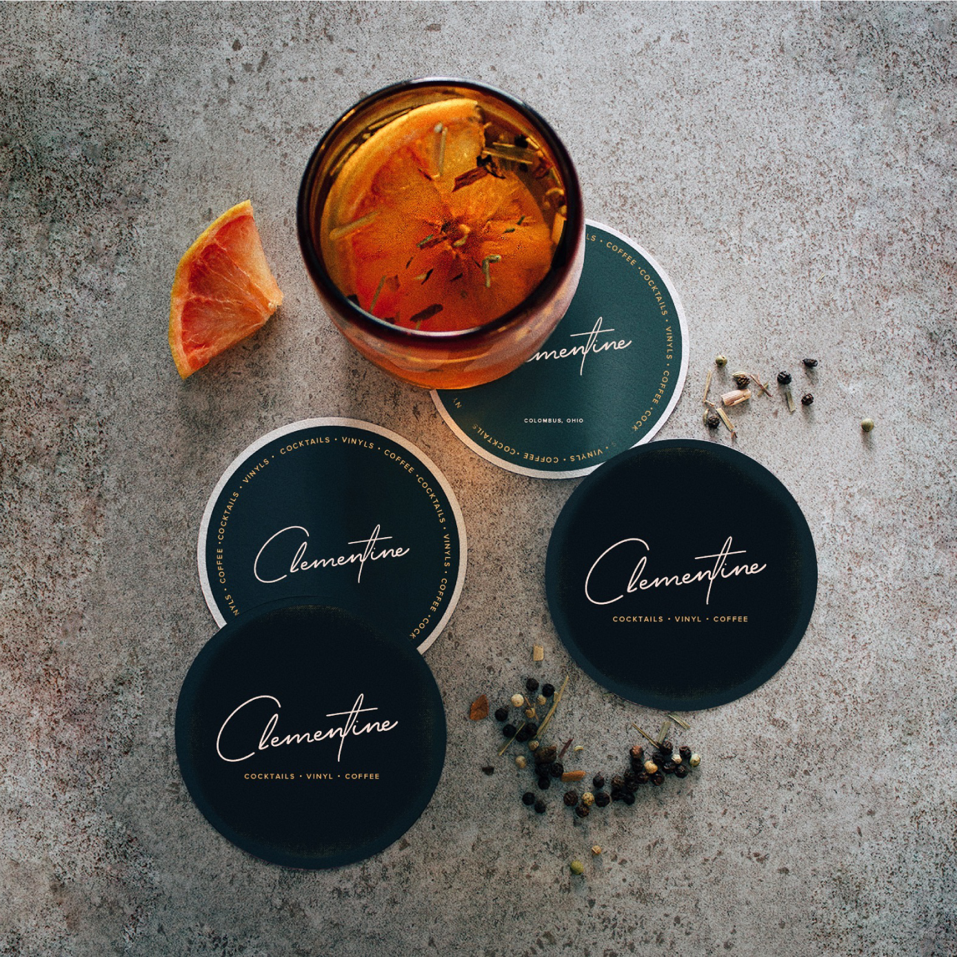 Clementine logo on Coasters near a cocktail