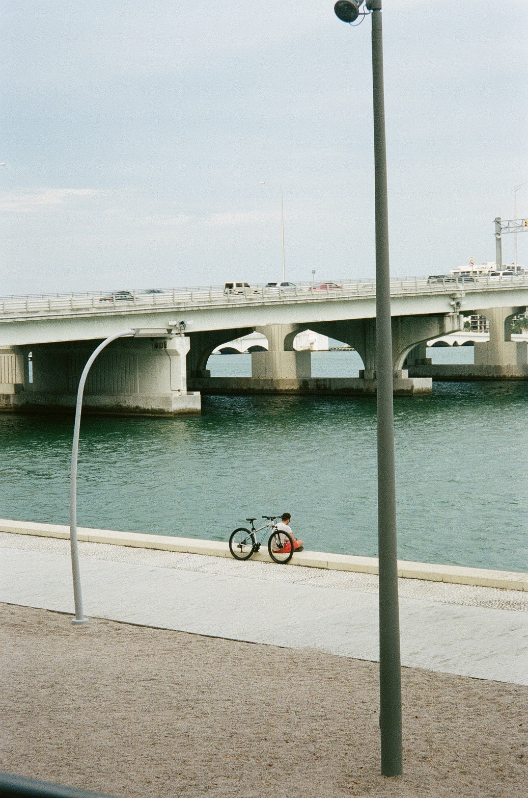 Film photo of man sitting by the water outside of the Perez Art Museum in Miami