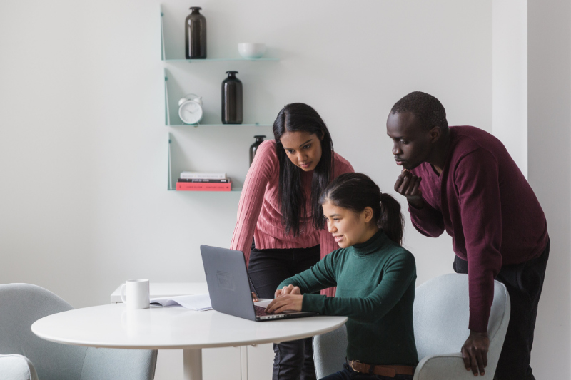 Three co-workers looking at a laptop screen