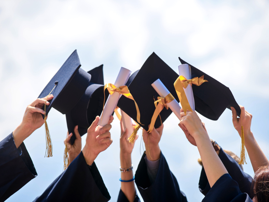 Eight students holding their graduation caps and diplomas in the air.